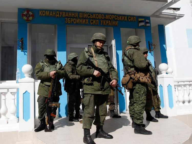 Armed men, believed to be Russian servicemen, stand guard by the entrance to the naval headquarters in Sevastopol