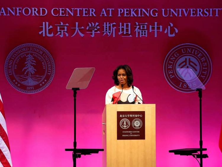 U.S. first lady Michelle Obama speaks next to American and Chinese national flags at Peking University in Beijing