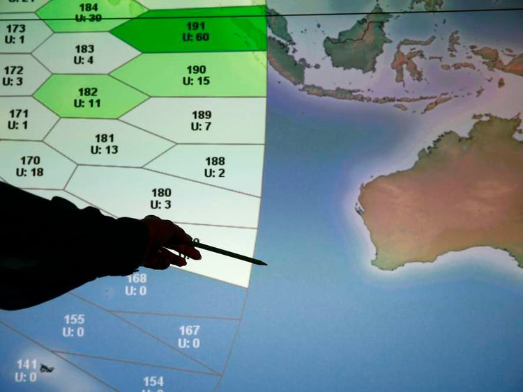 A member of staff at satellite communications company Inmarsat poses in front of a section of the screen showing the southern Indian Ocean to the west of Australia, at their headquarters in London