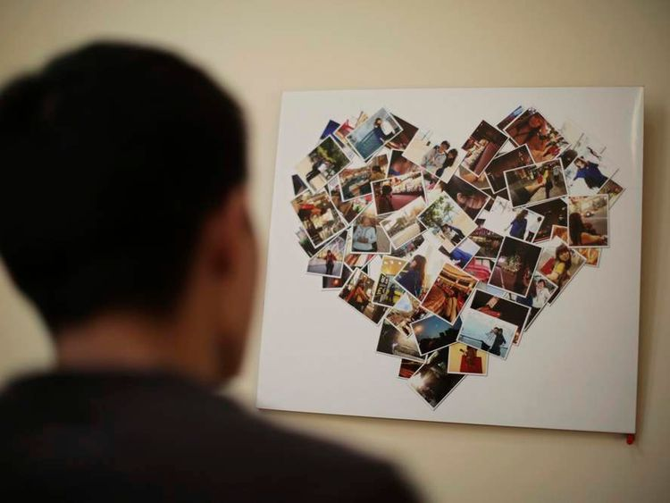 Zhang looks at a board covered with pictures of his fiancee Li, a passenger on board the missing Malaysia Airlines MH370, at their leased apartment in Tianjin