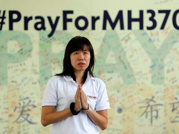 A woman prays for passengers onboard the missing Malaysia Airlines flight MH370 at Kechara retreat centre in Bentong