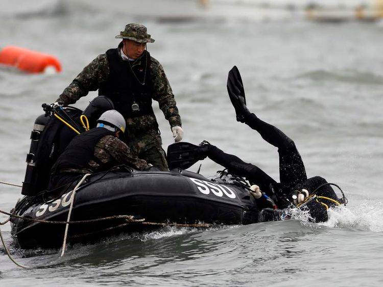 A member from the South Korean Navy's SSU dives into the sea off Jindo