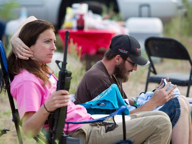 """Shelton interacts with his son as his mother holds his rifle during a Bundy family """"Patriot Party"""" near Bunkerville, Nevada"""