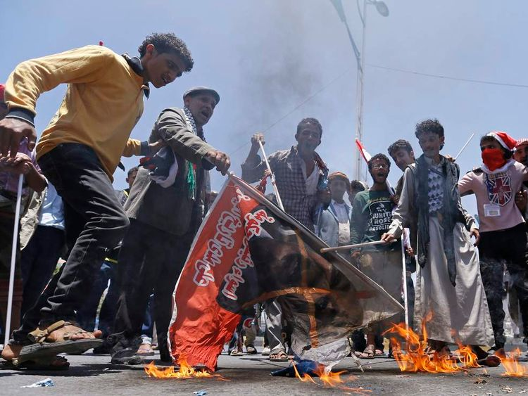 Anti-government protesters burn a poster of Yemen's PM Basindwa during a demonstration demanding his resignation in Sanaa