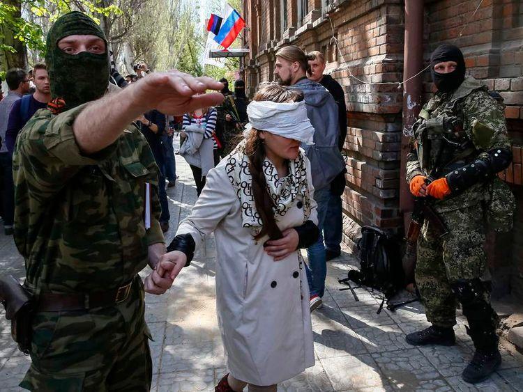 A pro-Russian armed man escorts Ukrainian journalist Irma Krat after a news conference in Slaviansk
