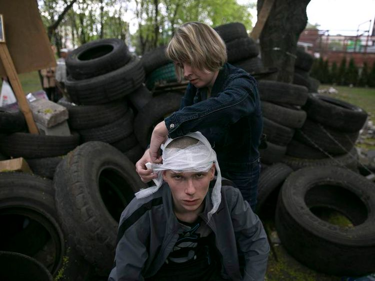 A woman bandages the head of a pro-Russian activist injured outside the Mariupol town hall, East Ukraine.