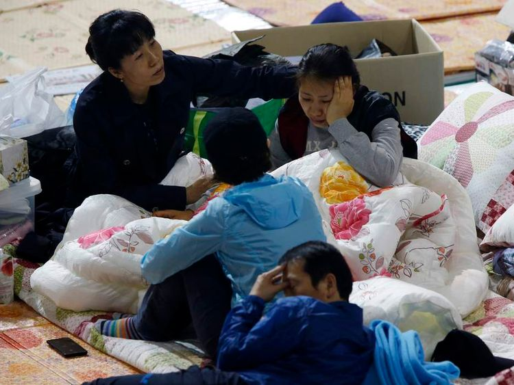 Family members of missing passengers onboard the sunken South Korean ferry Sewol, rest as they wait for news at a gymnasium in Jindo.