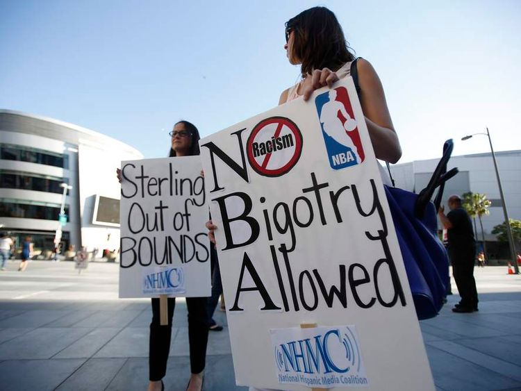 People hold signs before the NBA playoff game 5 between Golden State Warriors and Los Angeles Clippers in Los Angeles