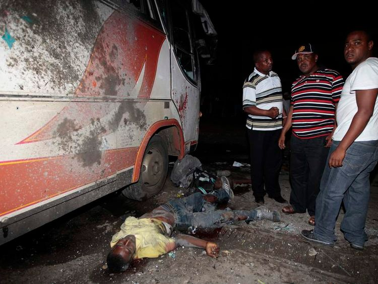 People stand next to the body of a man after an explosion at Mwembe Tayari