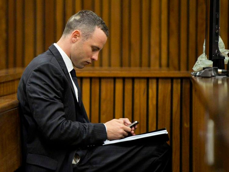 Oscar Pistorius uses a phone as he sits in court for his trial at the North Gauteng High Court in Pretoria