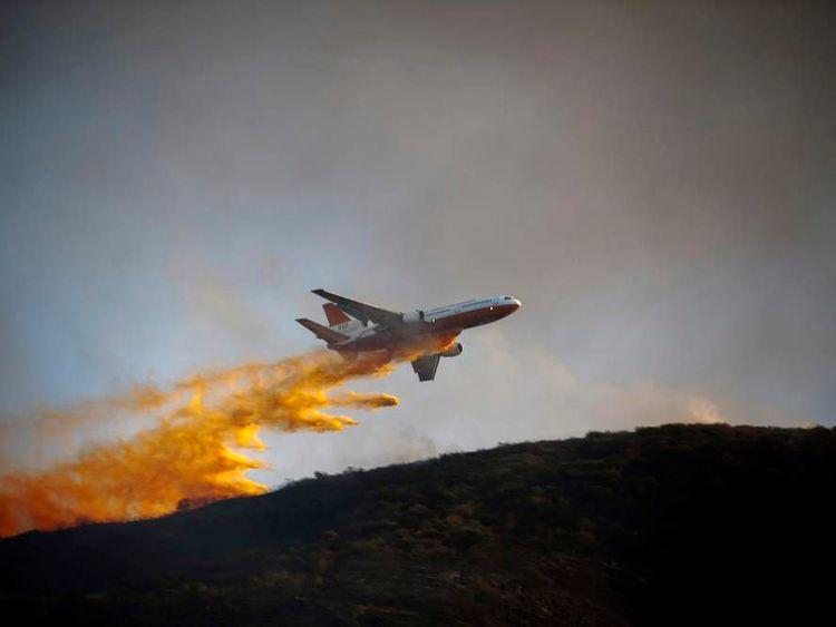 A DC-10 Super Tanker aircraft dumps flame retardant as firefighters battle a blaze in San Marcos