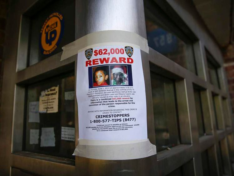 A NYPD reward poster is seen outside one of the Boulevard Houses public housing development in the East New York section of the Brooklyn borough of New York