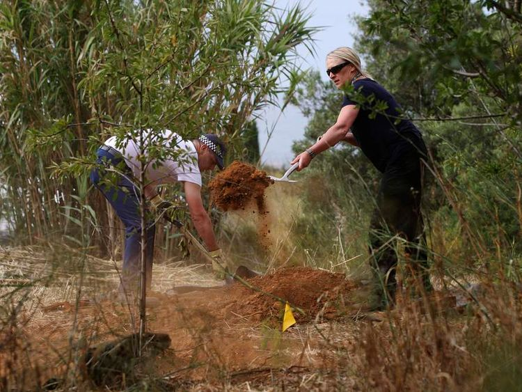 Members of Scotland Yard cover a hole during the search for missing British girl Madeleine McCann in Praia da Luz.