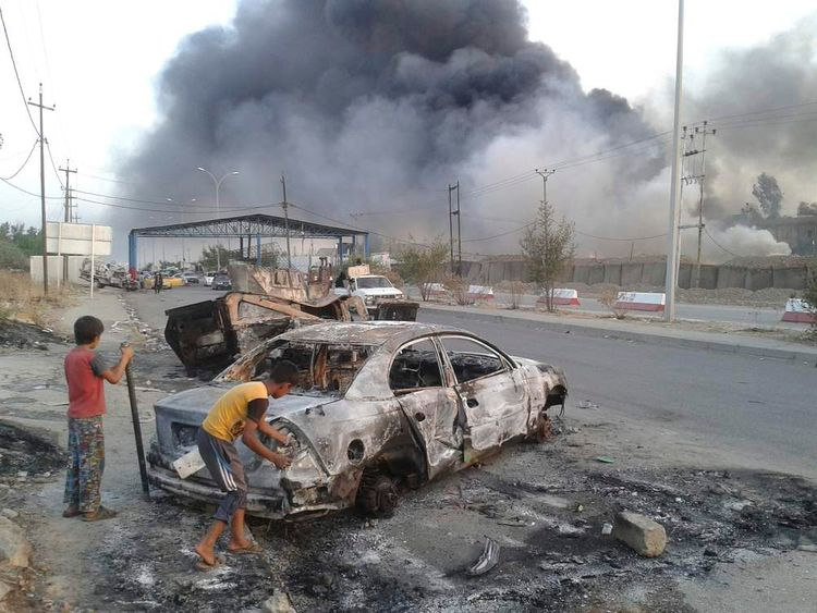 Civilian children stand next to a burnt vehicle during clashes between Iraqi security forces and al Qaeda-linked Islamic State in Iraq and the Levant (ISIL) in the northern Iraq city of Mosul