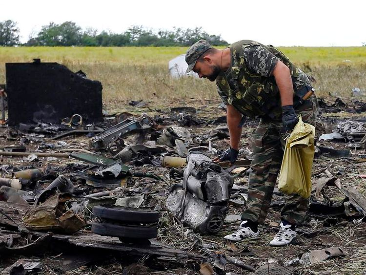 An armed pro-Russian separatist gathers ammunition at the site of the crash of the Il-76 Ukrainian army transport plane in Luhansk.