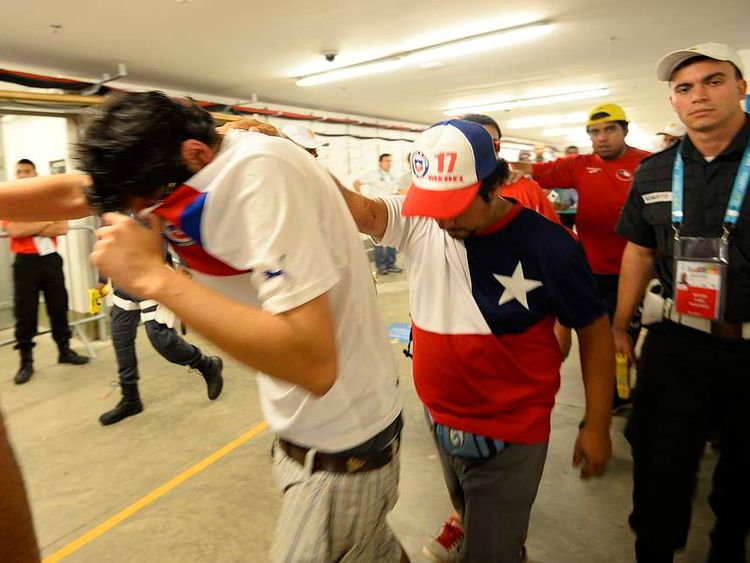 Chile fans are escorted by police after dozens of them crashed a gate to enter Maracana stadium