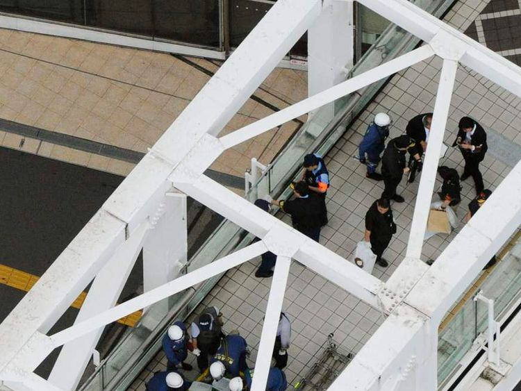 Police officers and fire-fighters investigate the site where a man set himself on fire at a pedestrian walkway near Shinjuku station in Tokyo