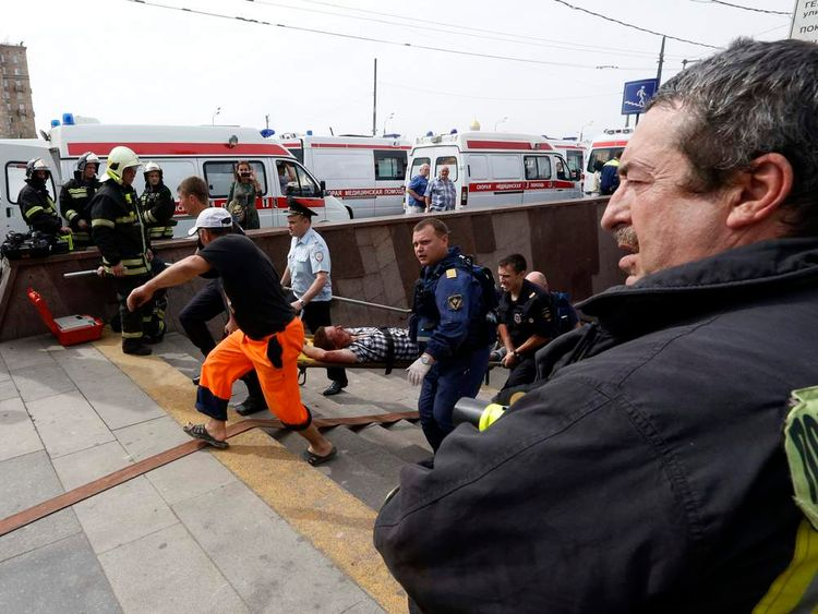 Members of the emergency services carry an injured passenger outside a metro station following an accident on the subway in Moscow