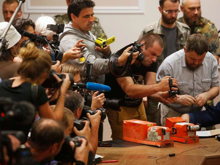 Photographers take pictures of black boxes from Malaysia Airlines MH17, before their handover from Ukrainian pro-Russian separatist to Malaysian representatives, in Donetsk