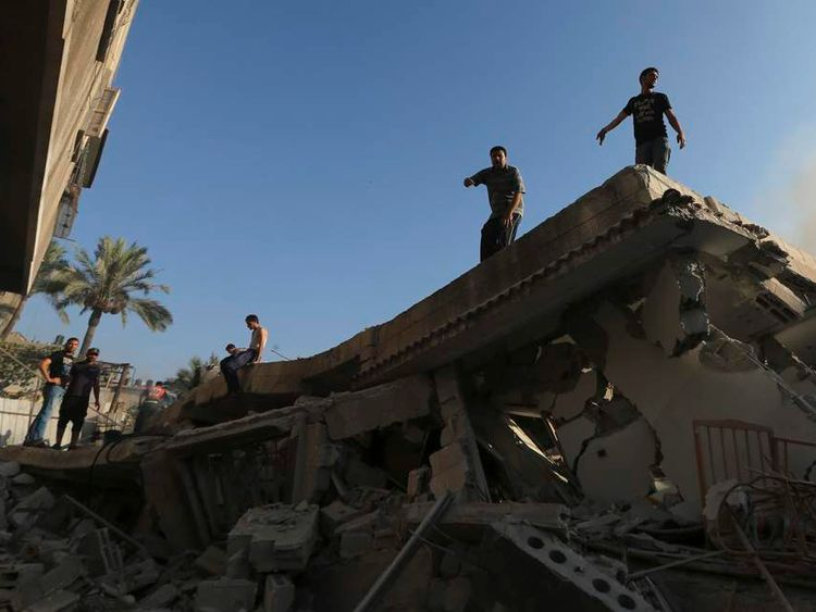 Palestinians stand atop the wreckage of a house in Gaza City.