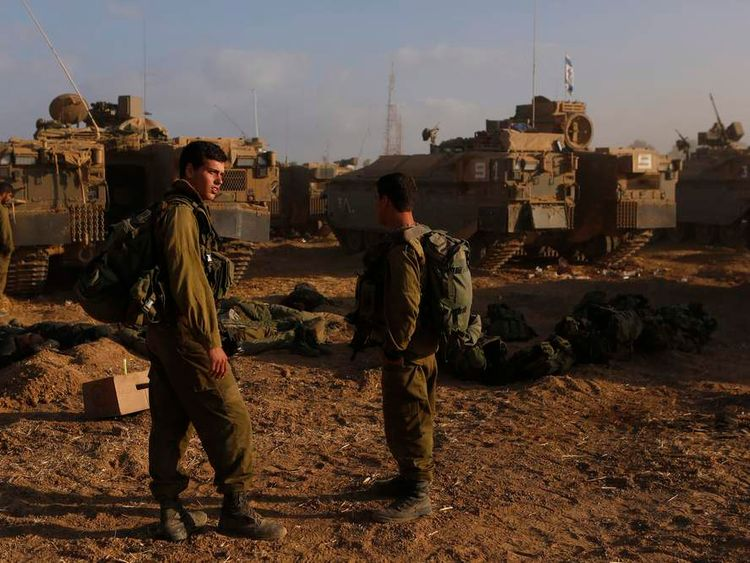 Israeli soldiers stand at a staging area near the border with the Gaza Strip