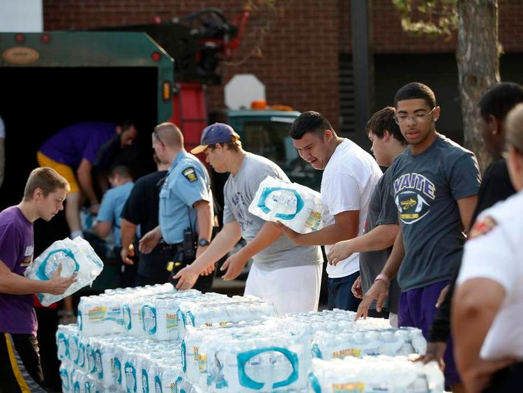 Volunteers unload drinking water from a truck outside Waite High School in Toledo