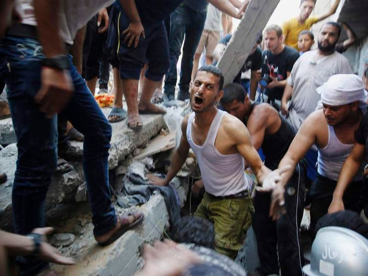 Palestinians dig through the rubble of a building in Gaza City