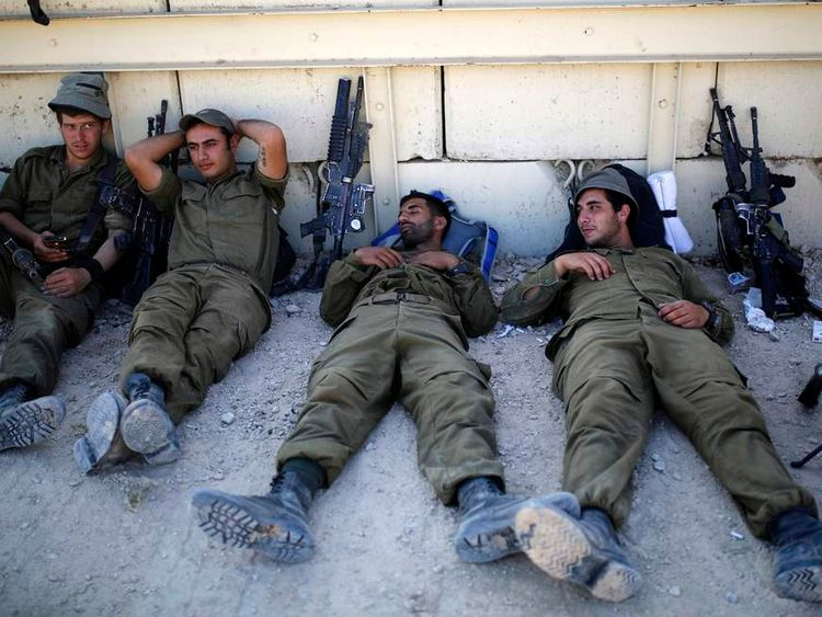 Israeli soldiers rest near the border with Gaza
