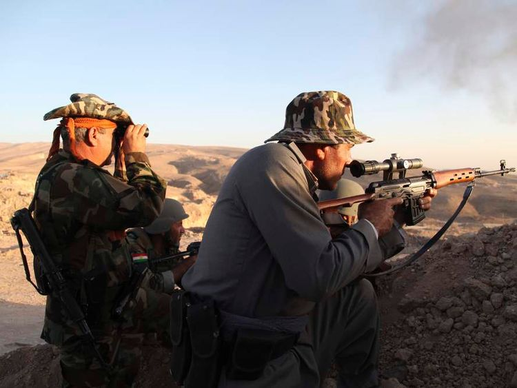 Iraqi Kurdish Peshmerga troops watch as smoke billows from the town of Makhmur