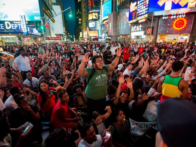 Protesters sit along a street during a peaceful demonstration, as communities react to the shooting of Michael Brown in New York's Times Square