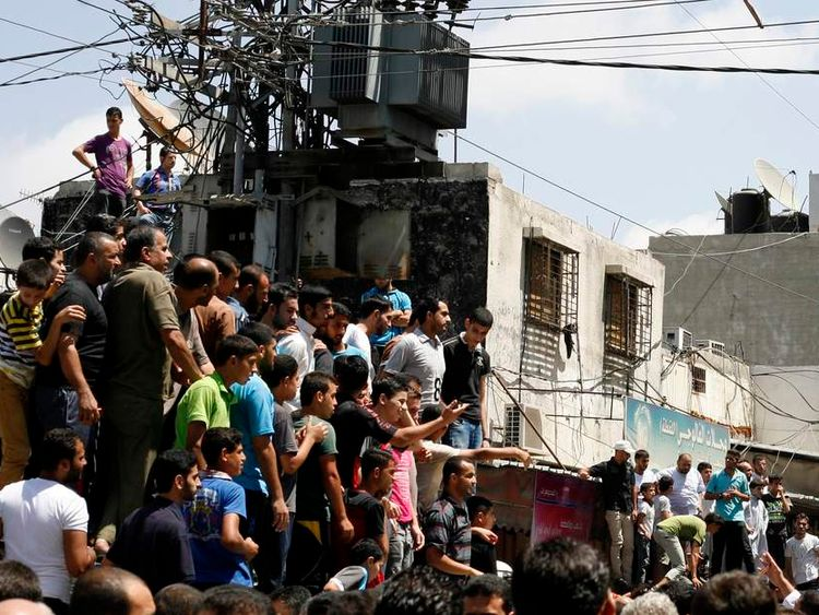 Palestinians watch as Hamas militants execute Palestinians suspected of collaborating with Israel in Gaza City
