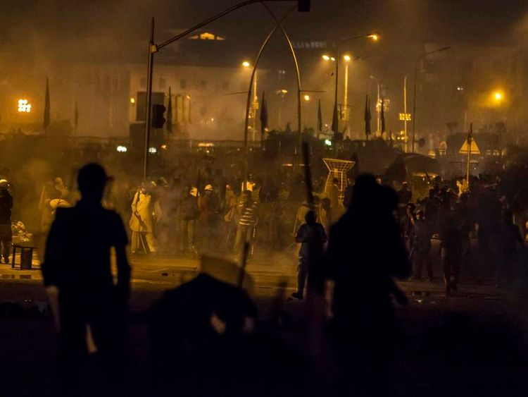Riot police clash with supporters of Qadri, Sufi cleric and leader of political party PAT, outside the parliament house as the supporters marched towards the prime minister's house in Islamabad