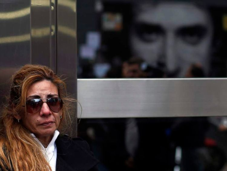 A woman cries as she stands outside the clinic where Argentine musician Gustavo Cerati died today in Buenos Aires