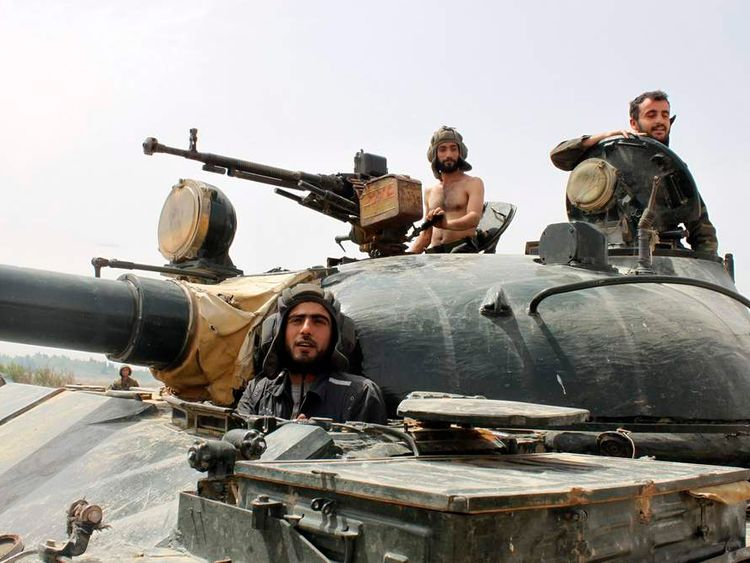 Forces of Syrian President Bashar al-Assad are seen in Arjoun village near Qusair town