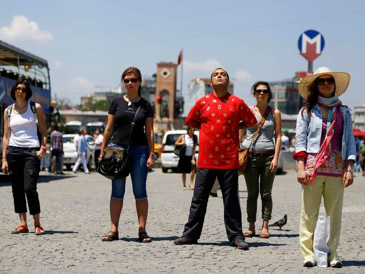 People stand in a silent protest at Taksim Square in Istanbul
