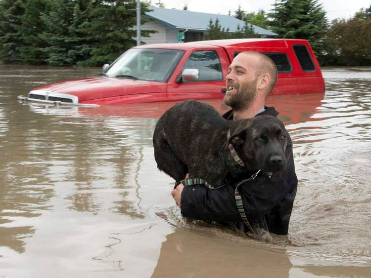 Man carries his dog to safety in High River in Alberta province