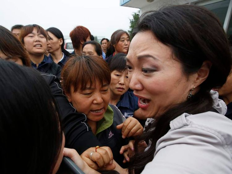 Workers push journalists at a Chinese factory where an American boss is being held over a pay dispute.