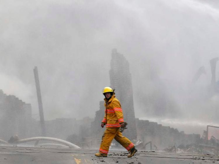 A firefighter walks past the remains of buildings after a train explosion at Lac Megantic