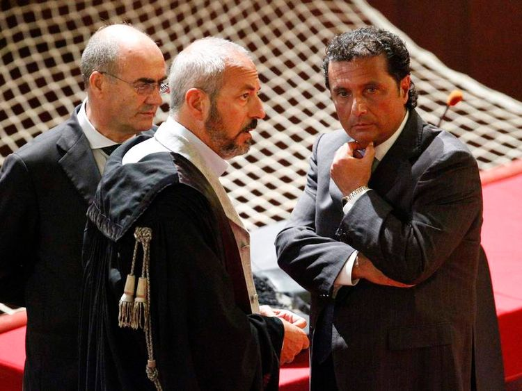 Schettino, captain of the Costa Concordia cruise ship, talks with his lawyers during a trial in Grosseto