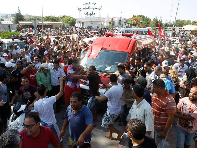 An ambulance carries the body of assassinated Tunisian MP Mohammed Brahmi