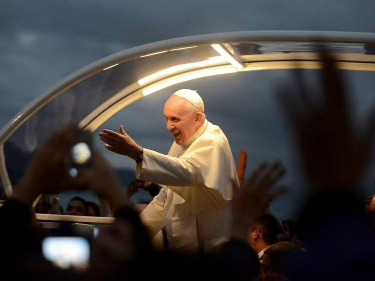 Pope Francis greets faithful as he is driven along the beachfront in the Copacabana neighborhood of Rio de Janeiro