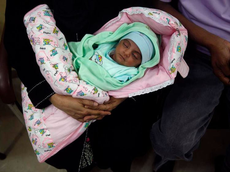 Fatima, a baby whom Pakistani television talk show host Hussain gave to a childless couple on his show, is held by her adoptive parents in Karachi