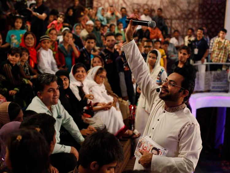 """Hussain, host of the Geo TV channel programme """"Amaan Ramazan"""", waves a microphone while asking participants questions during a live show in Karachi"""
