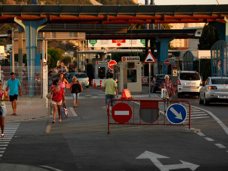 People are seen leaving and entering the British territory of Gibraltar at its border with Spain, in La Linea de la Concepcion