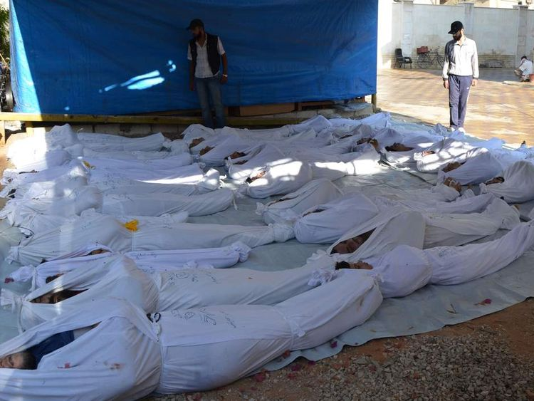 Syrian activists inspect the bodies of people they say were killed by nerve gas in the Ghouta region, in the Duma neighbourhood of Damascus