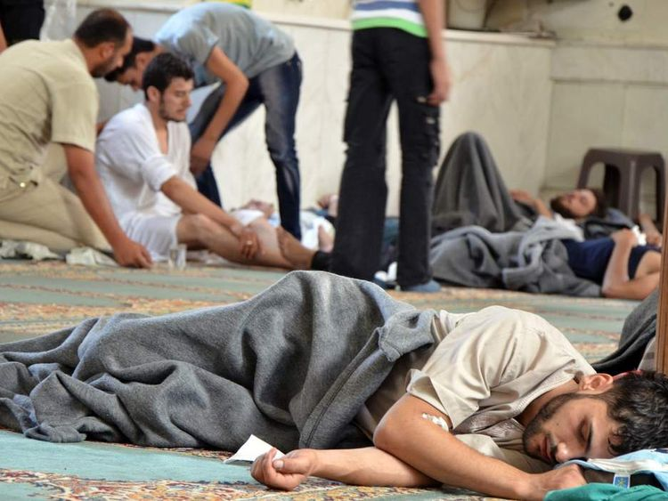 A survivor from what activists say is a gas attack rests inside a mosque in the Duma neighbourhood of Damascus