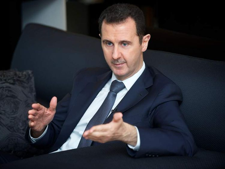 Syria's president Bashar al-Assad gestures during an interview with French daily Le Figaro in Damascus