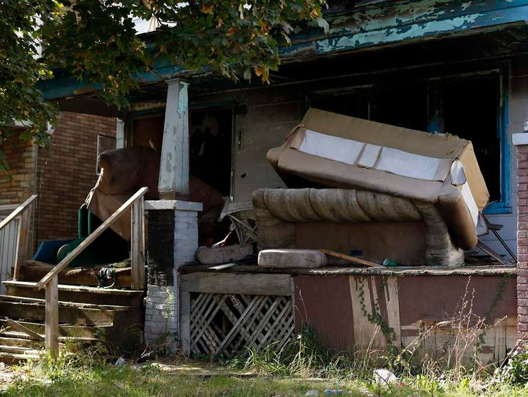 Abandoned furniture rest on the front porch of a blighted home in Detroit