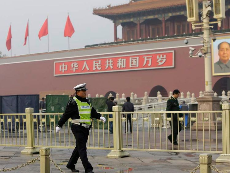 A policeman walks past in front of the giant portrait of the late Chinese chairman Mao as other policemen clean up after a car accident at the Tiananmen Square in Beijing