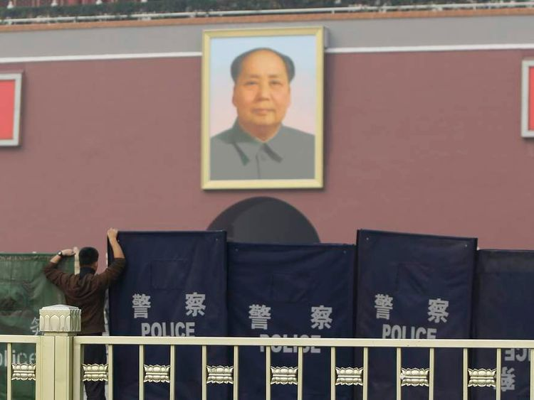 A police officer sets up barriers in front of the giant portrait of the late Chinese Chairman Mao Zedong as police clean up after a car accident at the Tiananmen Square in Beijing